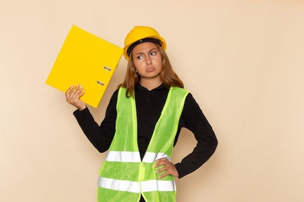 白い壁に黄色のドキュメント思考を保持している黄色いヘルメットの正面図女性ビルダー