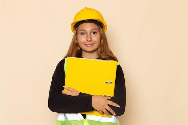 Вид спереди женщина-строитель в желтом шлеме, держащая желтый документ с улыбкой на белой стене