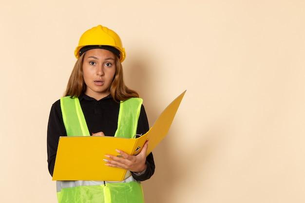 Вид спереди женщина-строитель в желтом шлеме, держащая желтый файл, записывающий заметки на белой стене