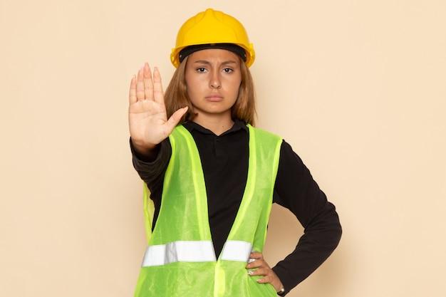 흰 벽 여성에 정지 신호를 보여주는 노란색 헬멧에 전면보기 여성 작성기