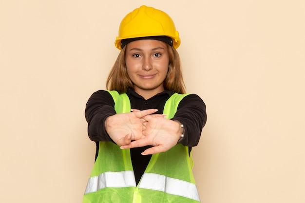 白い壁の女性に笑みを浮かべて黄色いヘルメットの正面図の女性ビルダー