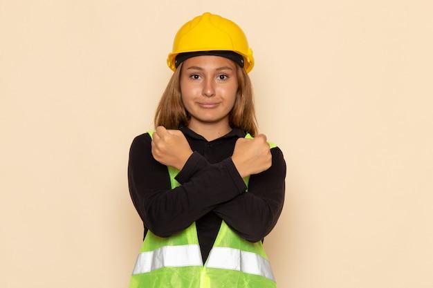 Вид спереди женщина-строитель в желтом шлеме, улыбаясь на белой стене