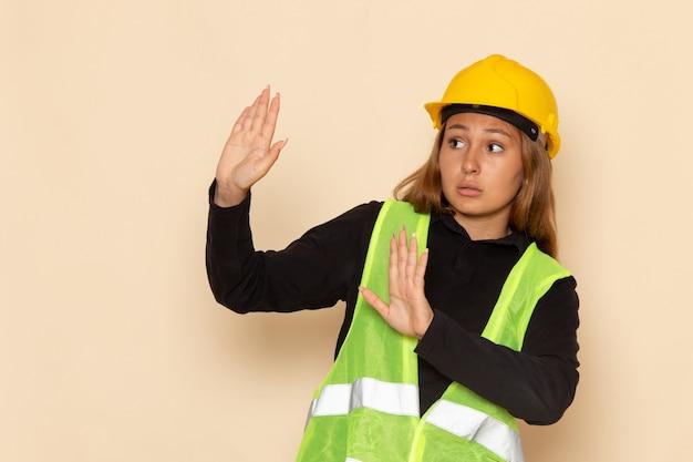 白い壁に慎重な表情で黄色いヘルメットの正面図の女性ビルダー