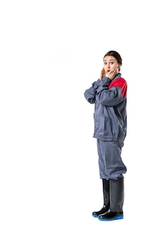 Front view of female builder in special uniform surprised on white wall