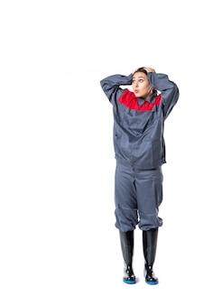 Vista frontale del costruttore femminile in uniforme speciale sul muro bianco