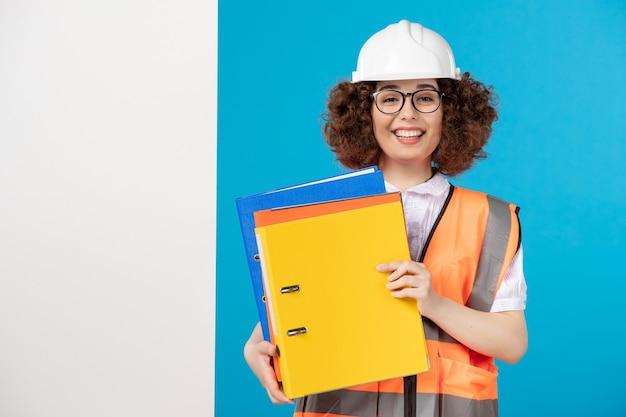 Vista frontale del costruttore femminile in uniforme sulla parete blu