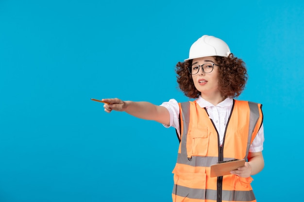 Front view female builder in uniform on a blue