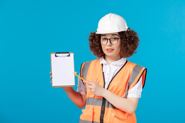 Front view female builder in uniform on blue