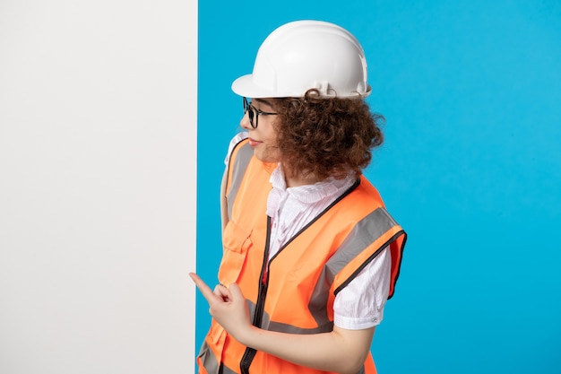 Front view female builder in uniform on the blue