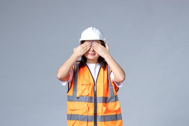 Vista frontale del costruttore femminile in uniforme che copre gli occhi sul muro grigio