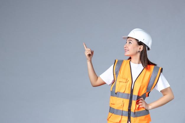 Vista frontale del costruttore femminile in uniforme sul muro grigio