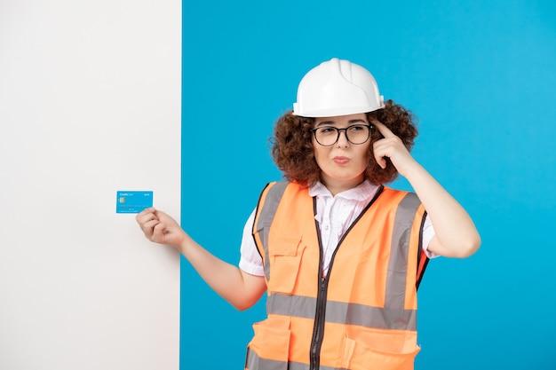 Vista frontale del costruttore femminile in uniforme e casco sulla parete blu