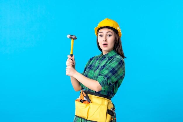 Costruttore femminile di vista frontale in uniforme che tiene martello sul blu