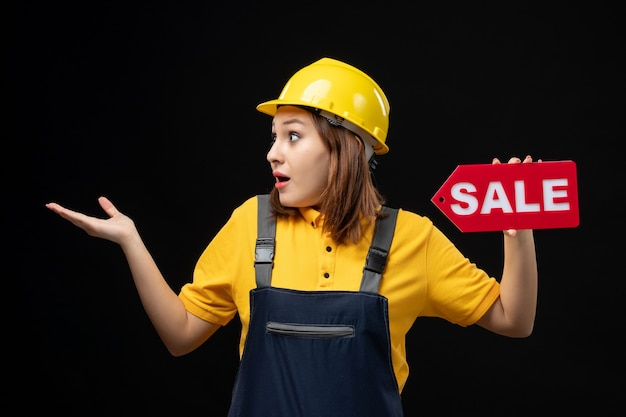 Front view female builder in uniform holding sale sign on black wall