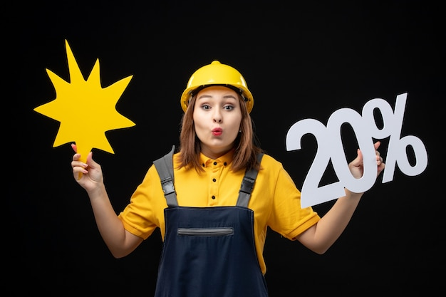 Front view female builder in uniform holding yellow figure and on black wall