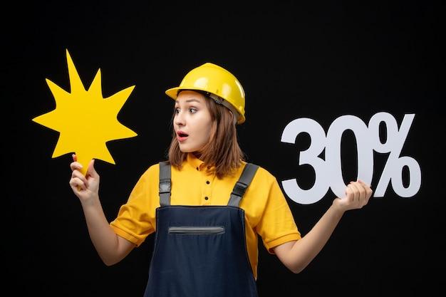 Costruttrice femminile vista frontale in uniforme che tiene una figura gialla sul muro nero