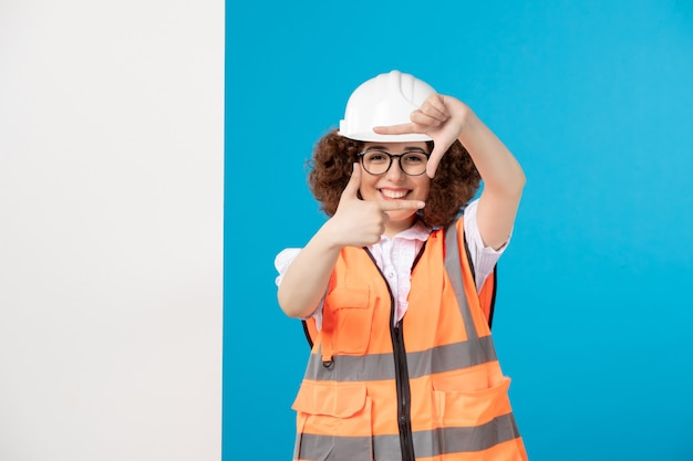 Costruttore femminile di vista frontale in uniforme che cattura maschera sull'azzurro