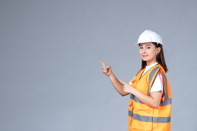 Front view of female builder in uniform on white wall