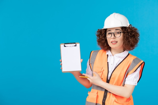 Front view female builder in uniform with note on blue
