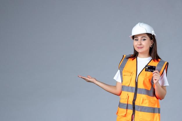 Vista frontale del costruttore femminile con carta di credito nera nelle sue mani sul muro grigio