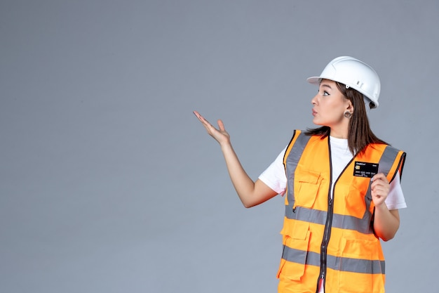 Front view of female builder with black bank card in her hands on gray wall