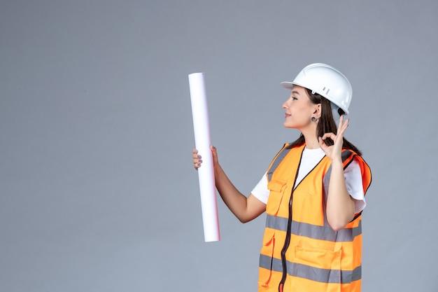 Vista frontale del costruttore femminile con poster in mano sul muro grigio