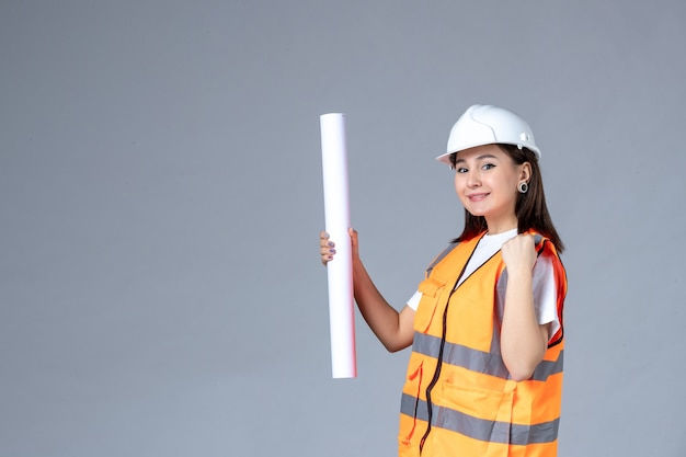 Front view of female builder with poster in her hands on gray wall