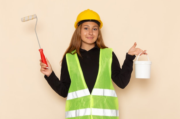 Front view female builder in yellow helmet black shirt holding paint and brush on white wall