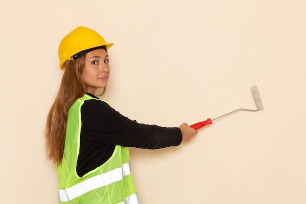 Costruttore femminile di vista frontale in pareti della pittura della camicia nera del casco giallo sullo scrittorio bianco