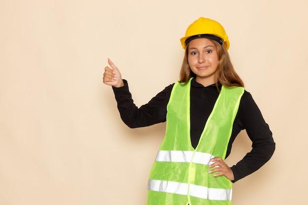 Costruttore femminile di vista frontale in camicia nera del casco giallo che posa mostrando come segno sulla parete bianca