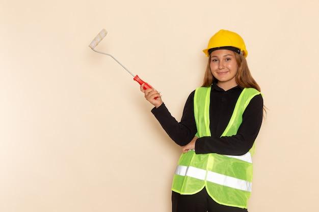 Costruttore femminile di vista frontale in pareti sorridenti della pittura della camicia nera del casco giallo sullo scrittorio bianco