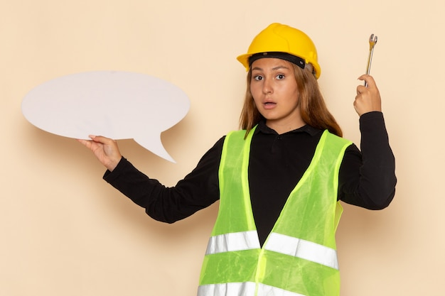 Costruttore femminile di vista frontale in casco giallo che tiene un grande strumento d'argento del segno bianco sull'architetto femminile della parete bianca