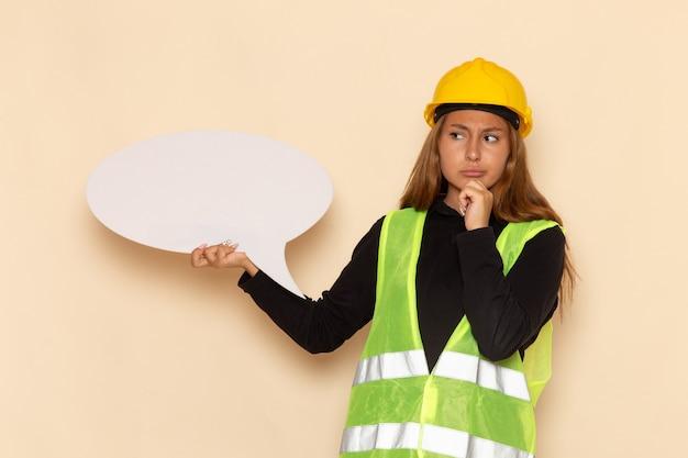 Costruttore femminile di vista frontale in casco giallo che tiene un grande segno bianco e che pensa sull'architetto femminile della parete bianca