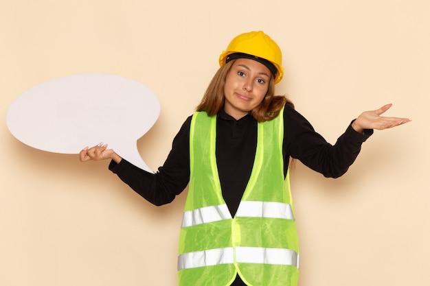 Costruttore femminile di vista frontale in casco giallo che tiene grande segno bianco sull'architetto femminile della parete bianca