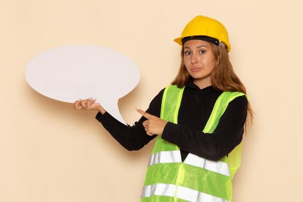 Costruttore femminile di vista frontale in casco giallo che tiene un grande segno bianco sull'architetto femminile della costruzione del costruttore della parete bianca