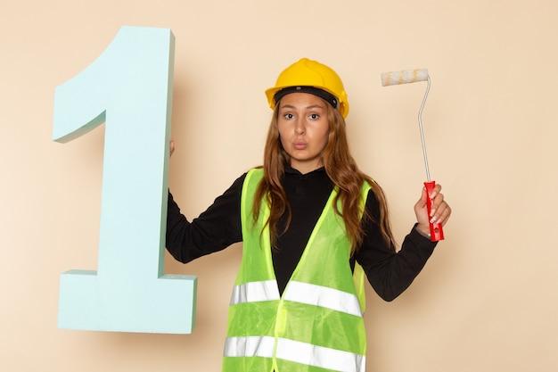 Costruttore femminile di vista frontale in casco giallo che tiene pennello e figura numero uno sul muro bianco