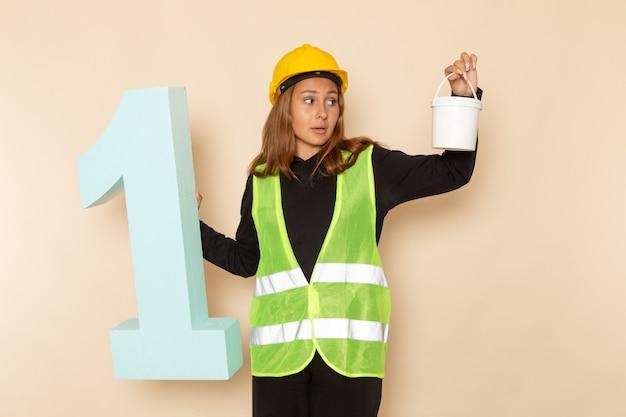 Costruttore femminile di vista frontale in casco giallo che tiene vernice e numero uno figura sul muro bianco