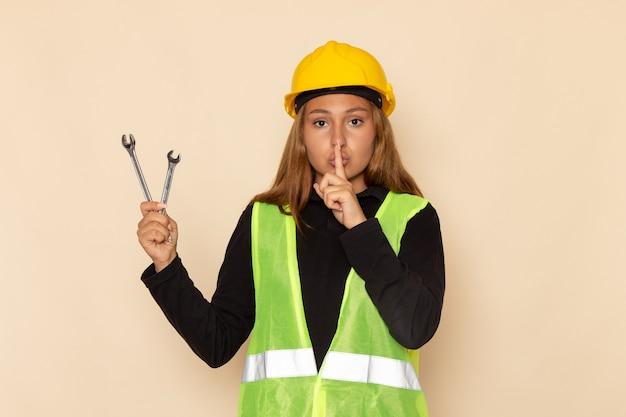 Costruttore femminile di vista frontale in casco giallo che tiene strumenti d'argento che mostrano il segno di silenzio sull'architetto femminile della parete chiara