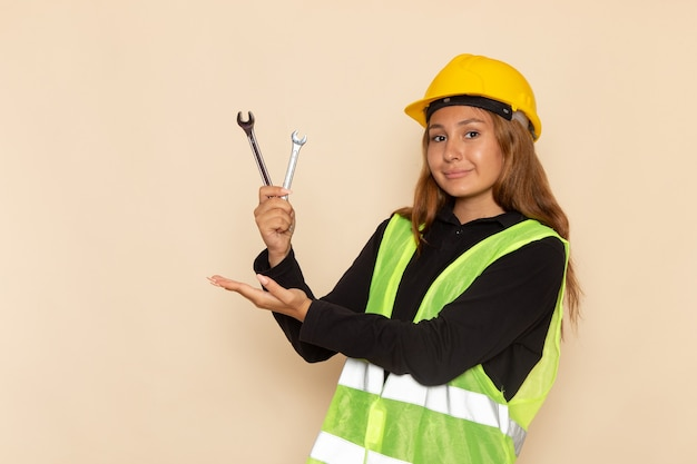 Front view female builder in yellow helmet holding silver instruments with smile on light wall female  architect