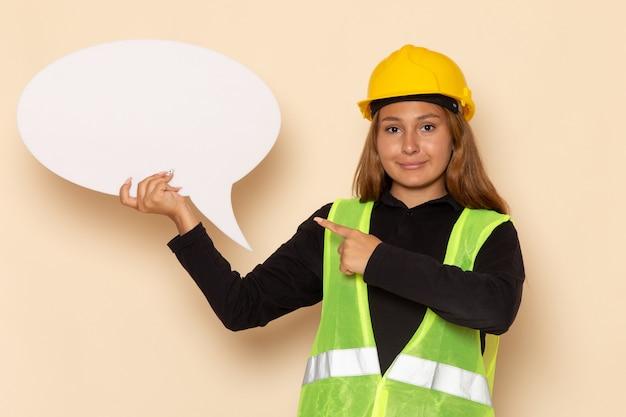 Costruttore femminile di vista frontale in casco giallo che tiene segno bianco sull'architetto femminile della parete bianca