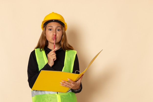 Front view female builder in yellow helmet holding yellow document and pencil on white wall