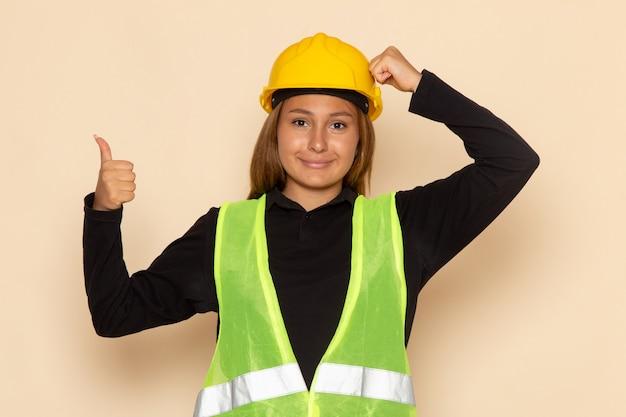 Costruttore femminile di vista frontale in casco giallo che sorride mostrando come segno sulla parete bianca