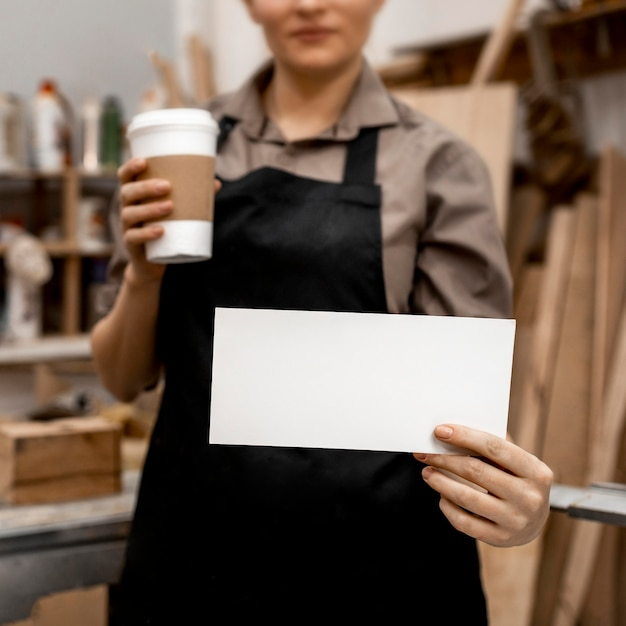 Front view of female carpenter holding coffee and paper
