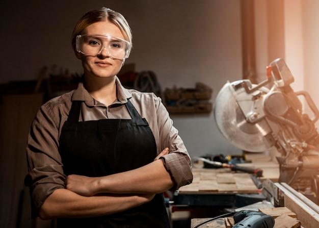 Vista frontale del falegname femminile in posa sul lavoro