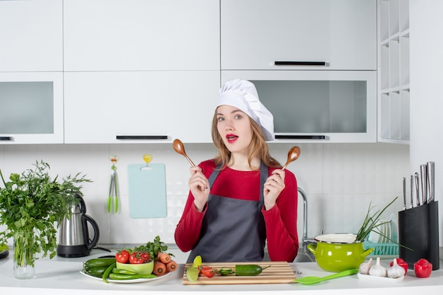 Front view female chef in apron holding wooden spoons in kitchen