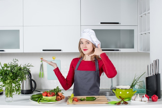 Front view female chef in apron making call me gesture