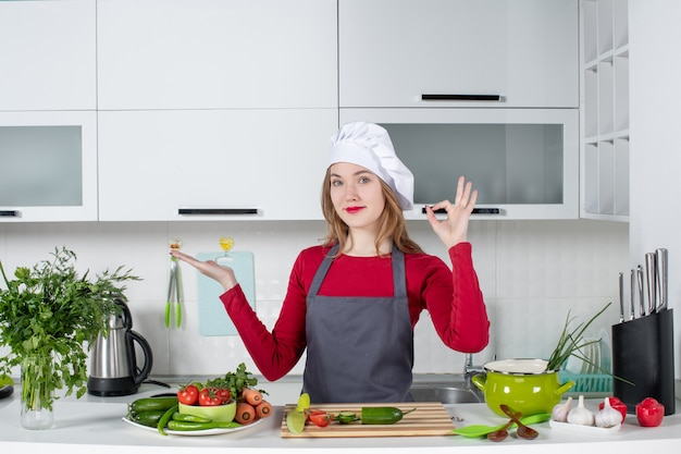 Front view female chef in apron making okey sign