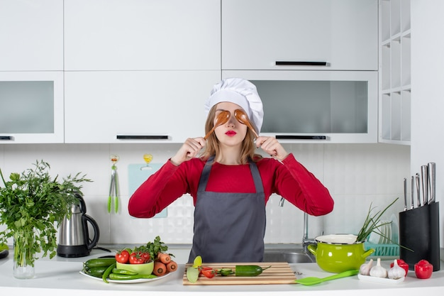 Front view female chef in apron putting spoons in front of her eyes
