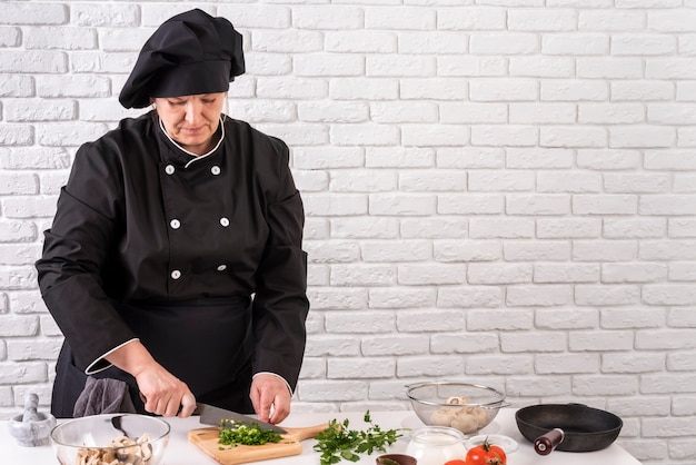 Front view of female chef chopping greens