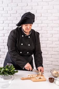 Vista frontale del cuoco unico femminile che taglia i funghi a pezzi